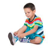 Cute boy tying shoelaces. A cute boy tying shoelaces on the white background royalty free stock image