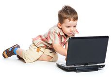 A cute boy is typing on a laptop Stock Image