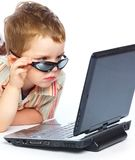 A cute boy is typing on a laptop Stock Images