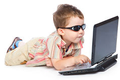 A cute boy is typing on a laptop Royalty Free Stock Photos