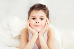 Cute boy under a blanket in bed in the bedroom. Lying on bed.  T Stock Images