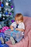 Cute boy unpacking Christmas presents. stock photos