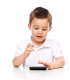 Cute boy is using calculator Royalty Free Stock Photography