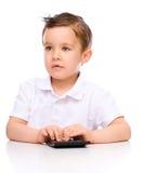 Cute boy is using calculator Stock Photo