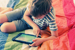 Cute boy. Using an electronic device Royalty Free Stock Image