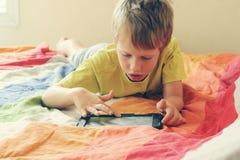 Cute boy. Using an electronic device Stock Image
