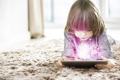 Cute boy using illuminated tablet while lying on rug at home Royalty Free Stock Photography