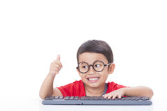 Cute Boy using a keyboard Stock Images