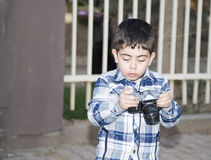 Cute boy using and playing with camera Stock Photography