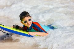 Boy swimming on boogie board. Cute boy on vacation having fun swimming on boogie board Royalty Free Stock Photography