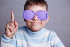 Cute boy in violet sunglasses with opaque lenses pointing upward royalty free stock photos