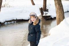Cute boy walking along a frozen brook on a winter day Stock Image
