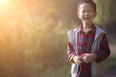 Cute boy walking in sunset with smile Royalty Free Stock Image
