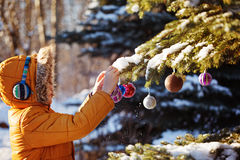 Cute boy in warm cloth and hat catching christmas ball in winter park. Kids play outdoor in snowy forest. Children catch christmas Royalty Free Stock Photo