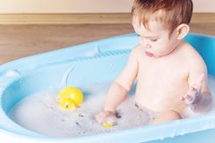 Cute boy washing in blue bath in bathroom. Baby is playing with a yellow duck and soap foam royalty free stock images