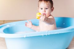Cute boy washing in blue bath in bathroom. Baby is playing with a yellow duck and soap foam. Cute baby boy washing in blue bath in bathroom. The child is playing stock photography