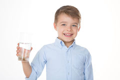 Cute boy with water. Boy holding a glass in his right hand Royalty Free Stock Photography