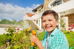 Cute boy watering garden with hand sprinkler royalty free stock photography