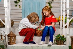 Cute boy with wavy hair and a girl with red hair sitting on the steps stock image