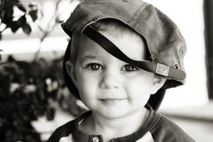 Cute boy wearing baseball hat. Black and white portrait of cute young boy wearing adult baseball cap back to front Royalty Free Stock Photography