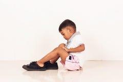 Cute boy wearing big shoe. School boy wearing big shoe Royalty Free Stock Photo