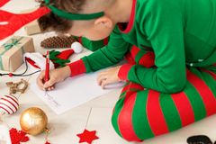 Cute boy wearing christmas pajamas writing letter to Santa on livingroom floor. Overhead view of a young boy writing wish list. stock photo