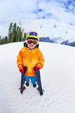 Cute boy wearing ski mask and helmet stands Stock Photos