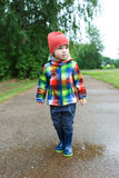 Cute boy in wellingtons walking after rain Royalty Free Stock Images