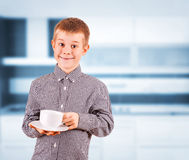 Cute boy with white cup of tea Royalty Free Stock Photography