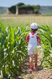 Cute boy with white hat and overalls, holding poppies, walking i Royalty Free Stock Photo