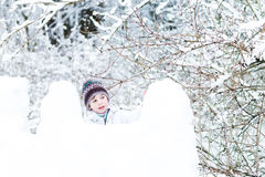 Cute boy in white jacket playing in a snow fort Royalty Free Stock Images