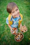 Cute boy with wild mushroom found in the forest Stock Images