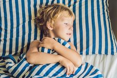 The cute boy woke up in his bed. Children sleep concept.  stock images