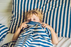 The cute boy woke up in his bed. Children sleep concept.  Stock Photos