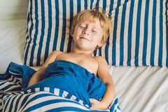 The cute boy woke up in his bed. Children sleep concept.  Royalty Free Stock Photography