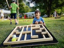 Festive games. Cute boy with wooden ball maze at outdoor festivals stock image