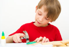 Boy working with hammer and nail Stock Images
