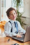 Cute boy working on a laptop. Smiling Stock Image