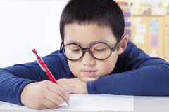 Cute boy writing on the paper in class Stock Images