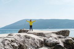 Cute boy 7 years old in a yellow jacket rais his hand up near th. E sea Stock Photography