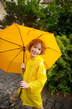The cute boy of 8-9 years under a yellow umbrella. The boy in a bright yellow raincoat holds a big umbrella in hand. The child looks in the camera with a smile Stock Photo