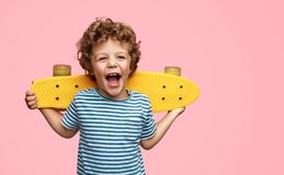 Cute boy with yellow skateboard. Funny little boy holding yellow skateboard on shoulders and screaming while standing on pink background royalty free stock photos