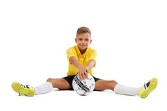 A cute boy in a yellow sports uniform holds a ball in his hands, young footballer isolated on a white background. Royalty Free Stock Images