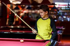 Cute boy in yellow t shirt plays billiard or pool in club. Young Kid learns to play snooker. Boy with billiard cue. Strikes the ball on table. Active Leisure royalty free stock photography