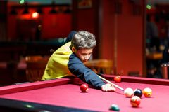 Cute boy in yellow t shirt plays billiard or pool in club. Young Kid learns to play snooker. Boy with billiard cue. Strikes the ball on table. Active Leisure royalty free stock photos
