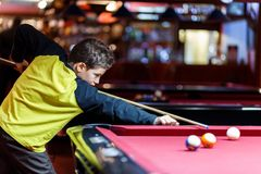 Cute boy in yellow t shirt plays billiard or pool in club. Young Kid learns to play snooker. Boy with billiard cue. Strikes the ball on table. Active Leisure stock photos