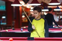 Cute boy in yellow t shirt plays billiard or pool in club. Young Kid learns to play snooker. Boy with billiard cue. Strikes the ball on table. Active Leisure royalty free stock image