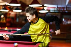 Cute boy in yellow t shirt plays billiard or pool in club. Young Kid learns to play snooker. Boy with billiard cue. Strikes the ball on table. Active Leisure royalty free stock images