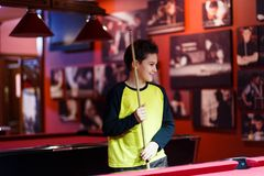 Cute boy in yellow t shirt plays billiard or pool in club. Young Kid learns to play snooker. Boy with billiard cue. Strikes the ball on table. Active Leisure stock image