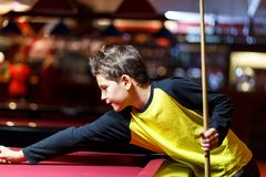Cute boy in yellow t shirt plays billiard or pool in club. Young Kid learns to play snooker. Boy with billiard cue royalty free stock photo